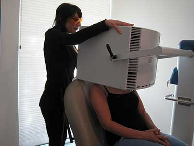 Esthetician Anne Marie Johnson performs a blue light therapy treatment on a patient.